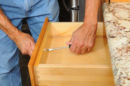 hardware: Primer plano de una instalaci�n de instalaci�n de hardware del gabinete caj�n de nuevos armarios de cocina. Formato horizontal, el hombre es irreconocible.