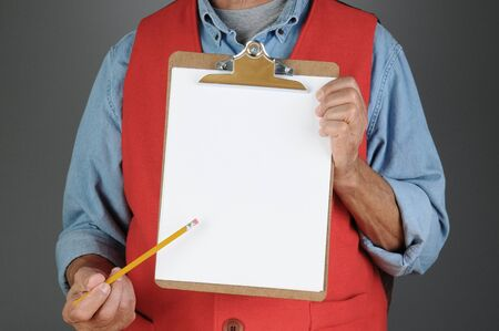 chrome man: Closeup of a hardware store worker holding a clip board and pointing to it with a pencil. Man is unrecognizable. Horizontal format with a light to dark gray background.
