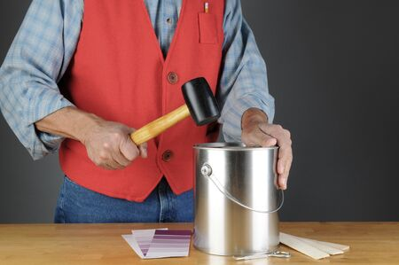 chrome man: Paint store employee pounding down the lid of a paint can. Horizontal format, with paint chips, opener and stir sticks on the counter. Man is unrecognizable.