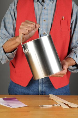 chrome man: Closeup of a paint store employee holding a paint can ready to hand to a customer. Vertical format, man is unrecognizable.