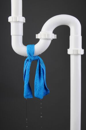 Closeup of a sink S Trap made of white PVC plastic with leak. A blue rag is wrapped around the pipes with water drips. Vertical Format.