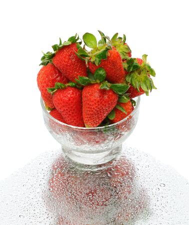 bruit: Closeup of fresh picked strawberries in a glass bowl with reflection on a wet surface over a white background.