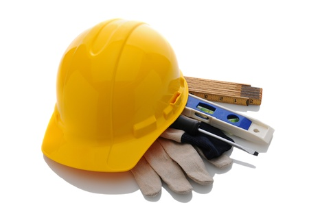 A yellow contractors hard hat on work gloves and tools. Horizontal format over white with reflection. Stockfoto