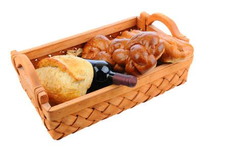 A basket with three loaves of bread and a bottle of red wine. Horizontal format isolated on white. photo
