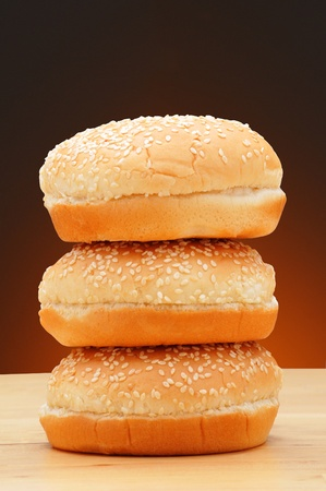 A stack of three hamburger buns with sesame seeds on a rustic wood surface and a light to dark warm background.