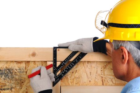 Closeup of a carpenter using a framing square to mark lines on the studs of a wall he is building. The man wearing a work shirt, gloves and a hard hat. Shallow depth of field with the focus on the hand and tool. photo