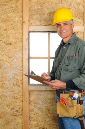 hard: A middle aged contractor standing in new construction writing on a clip board. Man is wearing jeans, work shirt, tool belt and a hard hat, and smiling at the camera. Vertical Format. Stock Photo