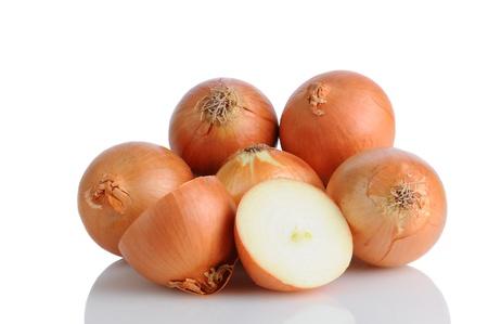 onions: Detalle de un montón de cebollas amarillas sobre una superficie blanca con la reflexión. Una cebolla se corta por la mitad formato horizontal. Foto de archivo