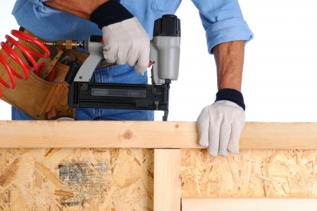 Closeup of a construction worker with a nail gun working on a wall he is building. Stockfoto