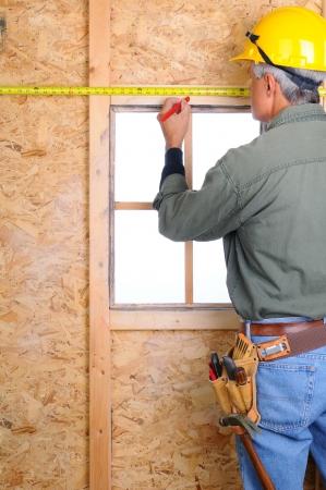carpintero: Primer plano de un trabajador de la construcci�n con una cinta m�trica que marca un punto en la pared