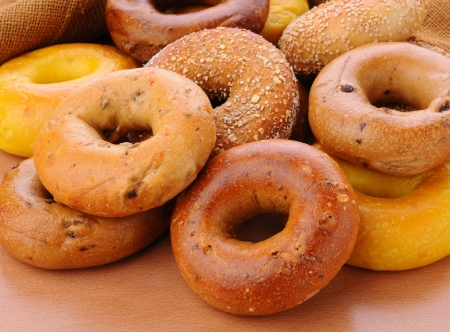 Closeup of a group of assorted bagels on a wood table top with burlap in the background  Bagels include, egg, whole grain, cinnamon raisin, sesame seed
