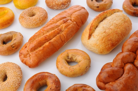 large group of items: A large group of breads and bagels viewed for overhead on white with reflection  Items include  sesame seed bagels, french breaad, italian bread, baguette and more Horizontal format that fills the frame  Stock Photo