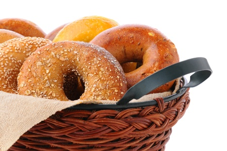 Closeup of assorted fresh bagels in a basket, including egg, sesame seed, multi-grain, plain, and cinnamon raisin