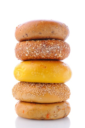 A stack of five different bagels on a white background with reflection  Bagels include  sesame seed, cinnamon raisin, multi grain, egg, and everything  photo