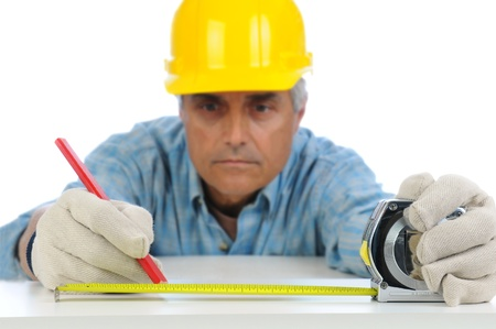 Closeup of a construction worker in hard hat using a measuring tape to mark cut line on a board  Focus is on the mans hands and tape measure  photo