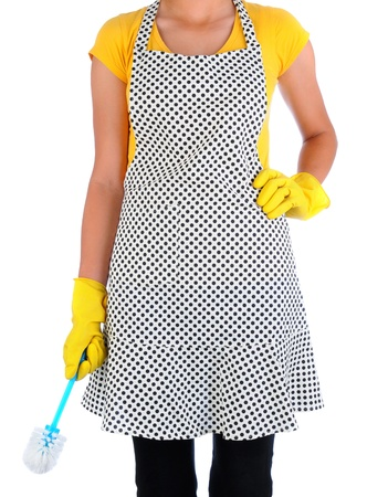 Closeup of a woman in an polka dot apron holding a toilet scrub brush  Woman has on yellow rubber gloves and is unrecognizable  Vertical format isolated on white