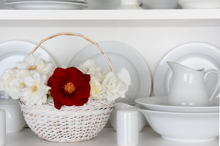 all in one: Closeup of a  basket of roses on the shelf of a cupboard full of white plates. Items include, plates, saucers, bowls and a gravy boat. There is one red rose amongst all the white. Stock Photo