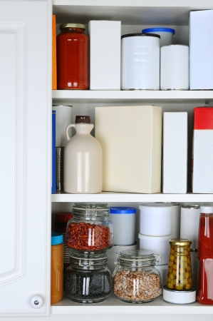 Closeup of a well stocked pantry. One door of the cabinet is open revealing canned goods, condiments, package foodstuffs, and storage jars. photo
