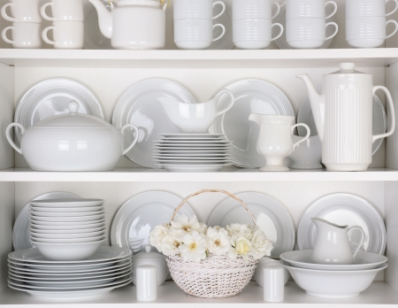 Closeup of white plates and dinnerware in a cupboard. A basket of white roses is centered on the bottom shelf.Items include, plates, coffee cups, saucers, soup tureen, tea pot, and gray boats.