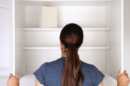 cereal box: Closeup of a woman looking in an empty pantry. Seen from behind there is only one box of food. Horizontal format.