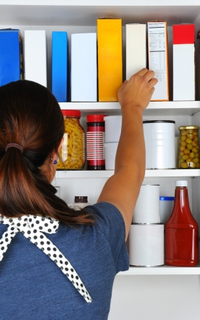 Closeup of a woman reaching into her pantry for a box of cereal. The well stocked cabinet is full of canned food, boxes, and bottles of typical grocery items. Items have blank labels. photo