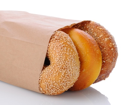 Closeup of three bagels in a brown paper bag laying on its side. Horizontal format on white with reflection. Zdjęcie Seryjne