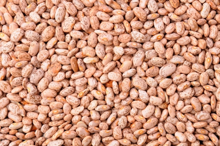 pinto: Closeup of a mass of pinto beans, fills the frame.