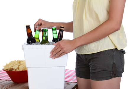 ice chest: Closeup of a woman taking a beer bottle from a styrofoam ice chest