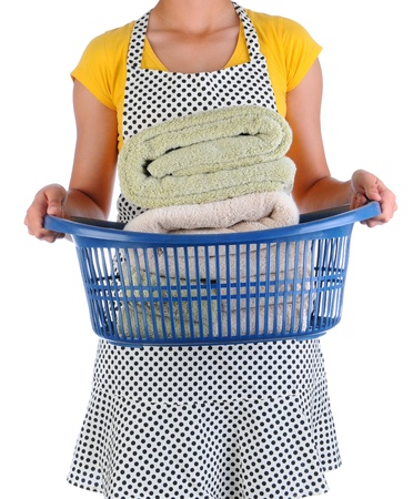 homemaker: Closeup of a housewife holding a laundry basket full of freshly laundered towels. Woman is unrecognizable.