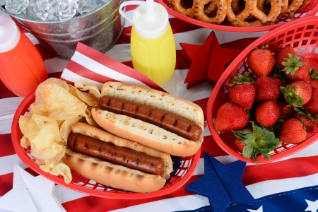 catsup: Looking down on a picnic table decorated for the 4th of July  Hot Dogs, chips, strawberries, mustard, ketchup, pretzels, and ice bucket fill the frame Stock Photo