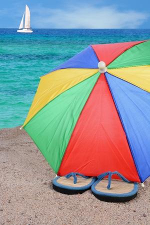 Closeup of a pair of flip-flops partially under a brightly colored beach umbrella Stock fotó