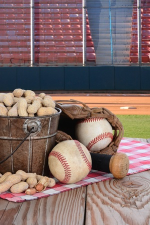 A bucket of peanuts and baseball equipment on a wood picnic table with a field and stadium in the background  photo