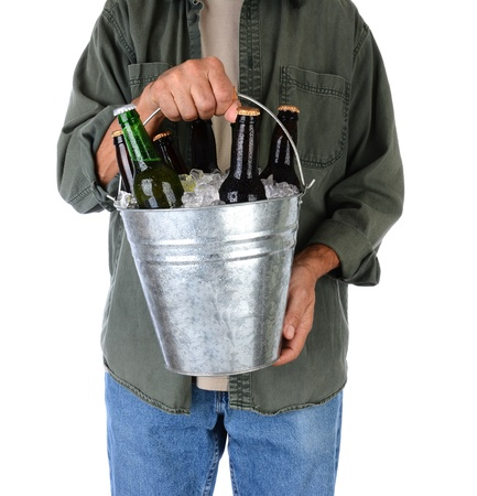 beer bucket: Closeup of a man holding a bucket of beer in front of his body  Man is wearing jeans and shirt with sleeves rolled up  Vertical format over white  Man is unrecognizable  Stock Photo