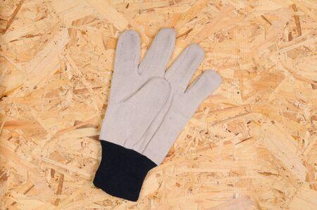 sheathing: Closeup of a single work glove on a a piece of strand board sheathing
