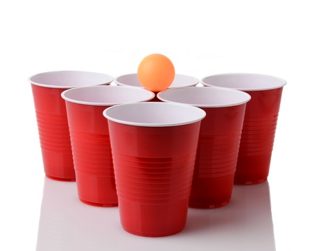 A yellow table tennis ball resting on a group of red plastic cups arranged for playing Beer Pong isolated on a white background with reflection