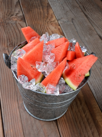 Closeup of a bucket filled with watermelon slices and crushed ice  The pail is sitting on a rustic wood picnic table  Vertical composition shot from a high angle  photo