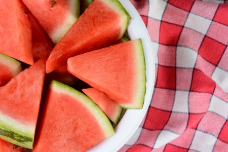 rind: Overhead shot of a bowl full of watermelon wedges on a checkered table cloth  Horizontal format  Half the bowl is shown, offset to one side of the frame