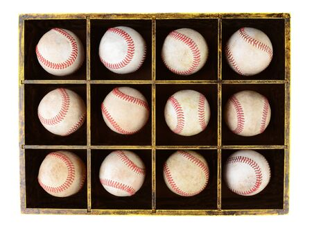 divided: A dozen scuffed baseballs in a divided wooden box  Horizontal format over white