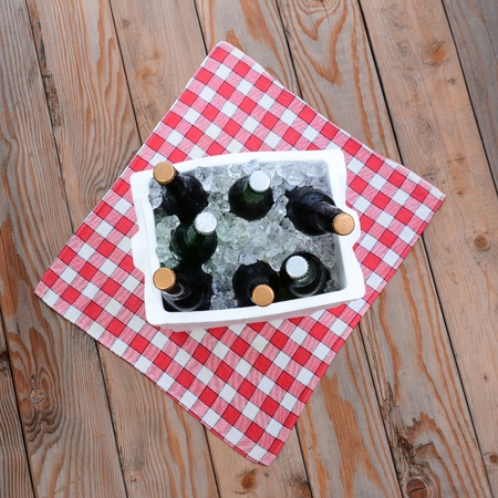 ice chest: Overhead shot of a ice chest full of beer bottles on a red and white checked table cloth on a wood deck  Square Format