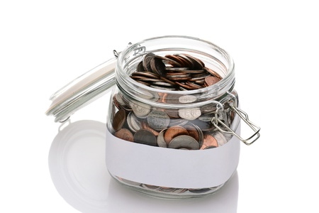Closeup of a mason jar filled with assorted coins  Lid is open and a blank label ready for your own text surrounds the container  Horizontal format isolated on white  Stock Photo