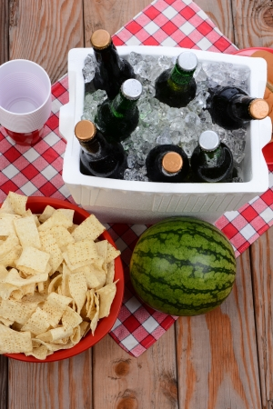 High angle shot of a picnic spread on a wood deck with red and white checkered table cloth  Items include  beer, ice chest, cups, chips and watermelon photo