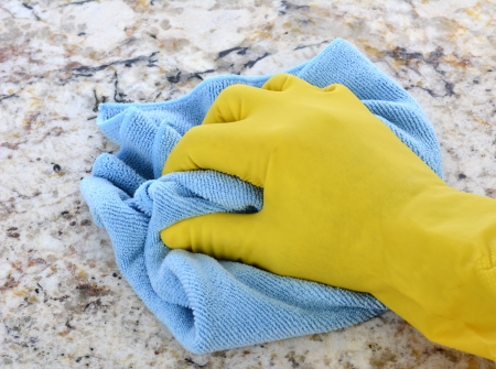 Closeup of a hand in a yellow latex glove using a blue towel to clean a granite counter top