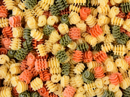 Tri-color Radiatore pasta, closeup filling the frame  Tomato, spinach and wheat pastas are shown, horizontal format  photo