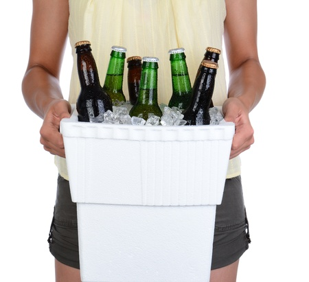 Closeup of a young woman carrying a box ice chest, over a white background  Cooler is full of ice and beer bottles  Woman is unrecognizable  photo