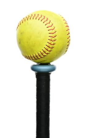 softbol: A softball amarillo usado descansando en el extremo mando de un bate de formato vertical de aluminio aislado en blanco Foto de archivo