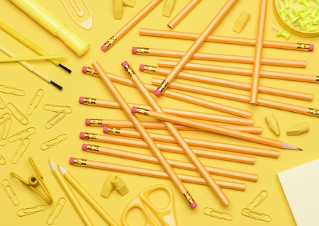 Yellow School Supplies  Pencils, erasers, paper clips, brushes, pins, scissors, paper laying in a random pattern on a yellow background  Closeup filling the frame with everything in a shade of yellow