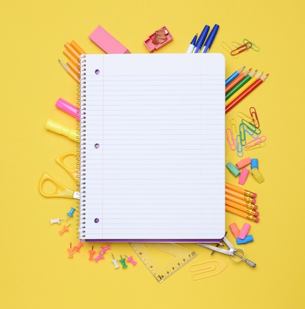 An open spiral notebook laying on assorted school supplies  Back to School concept  Equipment includes, pens, pencils, erasers, compass, scissors, paper clips and more  photo