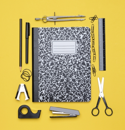 A closed theme book surrounded by school supplies including, compass, stapler, tape dispenser, pencil, paper clips, scissors  Back to School concept   Archivio Fotografico