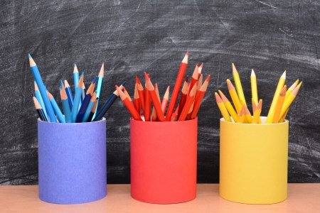 schoolroom: Closeup of colored pencils in matching pencil cups in front of a school room chalkboard  The cups are covered in red, blue and yellow construction paper and filled with the same color pencil