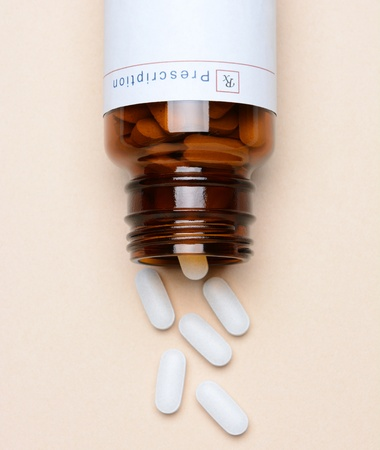 pills bottle: Overhead view of a glass prescription medicine bottle laying on its side with pills spilling onto the surface  Stock Photo
